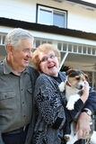 Elderly Couple with Dog. An upbeat joyful elderly man and woman couple in love at home with dog Royalty Free Stock Photo