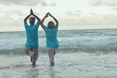 Elderly couple doing yoga on beach Royalty Free Stock Photo
