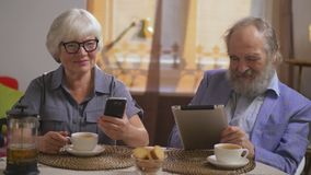 Elderly couple drink tea in their dining room sitting at a table with gadgets