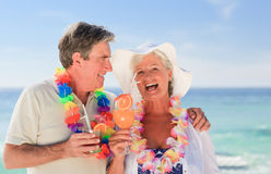 Elderly couple drinking a cocktail on the beach Stock Photo