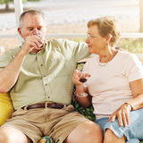 Elderly couple drinking on patio Stock Images