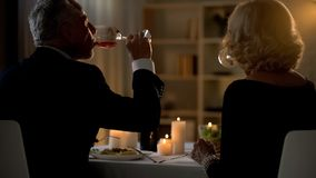 Elderly couple drinking red wine during romantic dinner, family tradition, love royalty free stock images