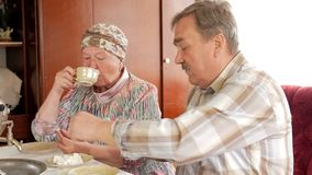An elderly couple is drinking tea from a vintage Russian kettle samovar. A man with a mustache talking with his wife in stock video