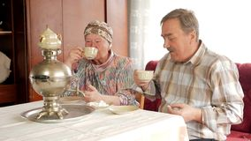An elderly couple is drinking tea from a vintage Russian kettle samovar. A man with a mustache talking with his wife in stock video footage