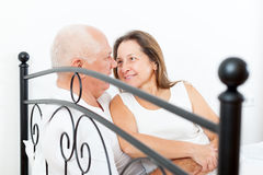 Elderly couple embracing in bed. Royalty Free Stock Image
