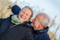 Elderly couple embracing and celebrating the sun Stock Images