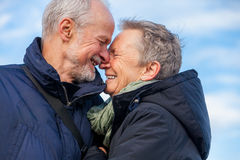 Elderly couple embracing and celebrating the sun. Attractive elderly couple in warm clothing standing clue together with outstretched arms, closed eyes and royalty free stock image
