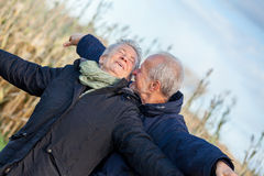 Elderly couple embracing and celebrating the sun Stock Photo