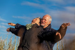 Elderly couple embracing and celebrating the sun Royalty Free Stock Images