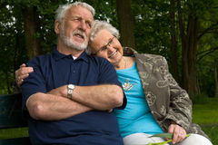 Elderly couple enjoying eachother. Outside portrait of an elderly couple on a bench stock images