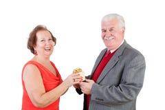Elderly couple exchange a valentine gift Royalty Free Stock Image