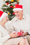 Elderly couple exchanging christmas gifts. On couch Royalty Free Stock Photos