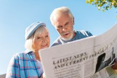 Elderly couple feeling excited while reading morning local news outside house. Local news. Elderly couple feeling truly involved and excited while reading royalty free stock photography