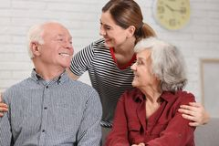 Elderly couple with female caregiver. At home stock images