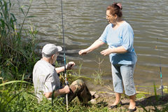 Elderly couple fishing on a freshwater lake Royalty Free Stock Photography