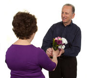 Elderly couple with flowers Stock Photography