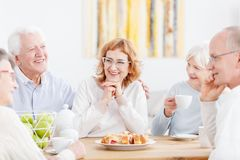 Elderly couple with friendly neighbors. Happy elderly couple talking and laughing at tea party with friendly senior neighbors royalty free stock photo