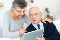 Elderly couple in front tablet stock photo