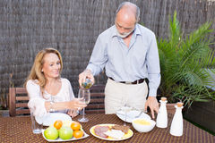 Elderly couple in garden. Drinking wine Stock Image