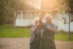 Elderly couple with garden hose. Stock Images