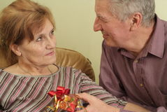 Elderly couple with a gift Stock Images
