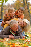 Elderly couple and grandchildren lie. Happy beautiful elderly couple and grandchildren lie in the autumn park royalty free stock images