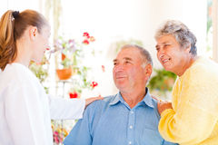 Elderly couple. Happy elderly couple talking with their carer stock photos