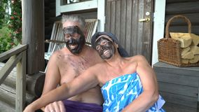 Happy seniors couple enjoys the sauna for wellness and health. The elderly couple are happy together sitting on the wooden steps of the Finnish sauna and using