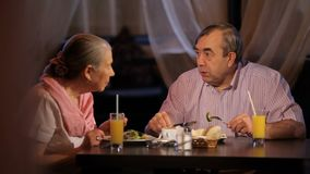 An elderly couple has dinner. In restaurant stock footage