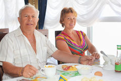 Elderly couple having breakfast at restaurant. Smiling elderly married couple having breakfast at restaurant near window royalty free stock image