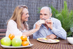 Elderly couple having food on terrace. Elderly couple in garden having some snacks Stock Photo