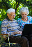 Elderly couple having fun with the laptop outdoors. An elderly couple having fun with the laptop in the garden, outside Royalty Free Stock Images