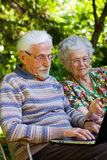 Elderly couple having fun with the laptop outdoors Royalty Free Stock Photo