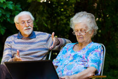 Elderly couple having fun with the laptop outdoors. An elderly couple having fun with the laptop in the garden, outside Royalty Free Stock Image
