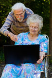 Elderly couple having fun with the laptop outdoors. An elderly couple having fun with the laptop in the garden, outside Royalty Free Stock Photos