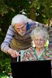 Elderly couple having fun with the laptop outdoors. An elderly couple having fun with the laptop in the garden, outside Stock Photos