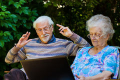 Elderly couple having fun with the laptop outdoors Stock Images