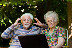 Elderly couple having fun with the laptop outdoors. An elderly couple having fun with the laptop in the garden, outside Royalty Free Stock Photo