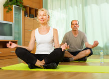 Elderly couple having yoga at home stock photography