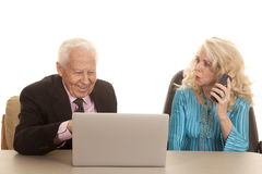 Elderly couple her on phone him computer Royalty Free Stock Images