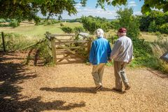 Elderly couple hold hands,walking in the British countryside royalty free stock photo