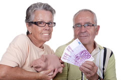 Elderly couple holding bills and piggy bank. Happy elderly couple holding bills and piggy bank Stock Images