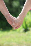 Elderly couple holding hands Stock Photos