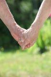 Elderly couple holding hands stock photos