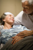 Elderly couple holding hands at clinic ward Stock Image