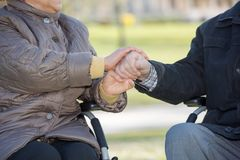 Elderly couple holding hands. Close-up royalty free stock image