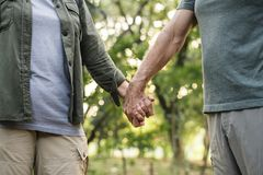 Elderly couple holding hands in the forest stock images
