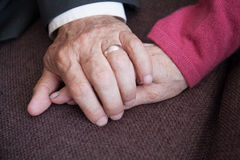 Elderly couple holding hands, indoor Royalty Free Stock Images