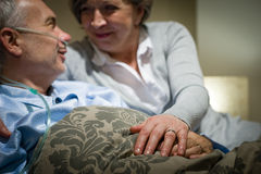 Elderly couple holding hands lying in bed Stock Photos