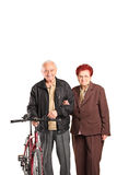 Elderly couple holding hands and pushing a bike Stock Photo